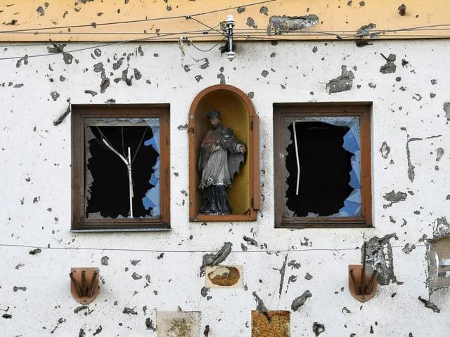 Beschädigte Fassade und zerstörte Fenster an einem Gebäude.