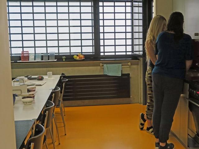 Zwei Frauen stehen in einer Küche und hantieren am Kochherd
