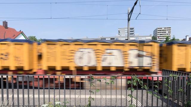 Ein Güterwagen fährt durch ein Wohngebiet. Vorne ist ein metallenes Gitter zu sehen. Der Güterwagen ist gelb.