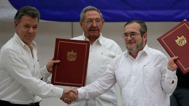 Der kolumbianische Präsident Juan Manuel Santos und der Farc-Chef Timoleon Jimenez präsentieren den Friedensvertrag.