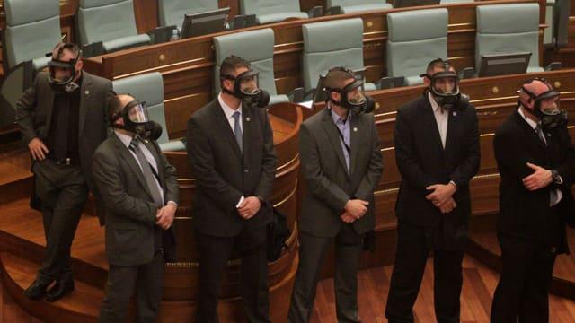 Das Sicherheitspersonal im kosovarischen Parlament mit Gasmasken.