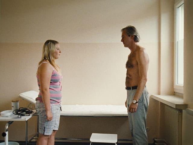 Melanie und der Arzt ((Joseph Lorenz) stehen sich im Behandlungszimmer gegenüber, er mit entblösstem Oberkörper.