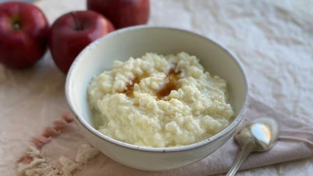 Ein Schälchen Milchreis mit Ahornsirup und Apfel. Im Hintergrund 3 rotschalige Äpfel.