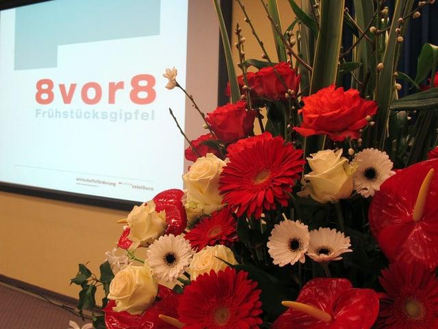 Blumen und im Hintergrund Logo 8 vor 8.