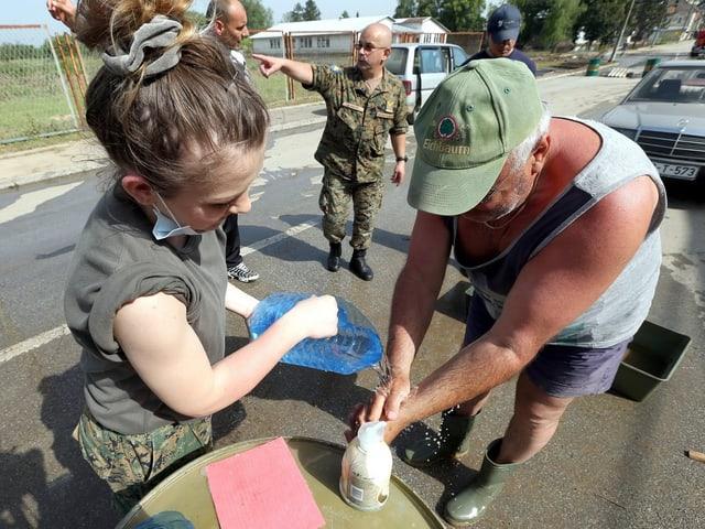 Eine Frau hilft auf offener Strasse einem Mann dabei, sich die Hände zu desinfizieren.