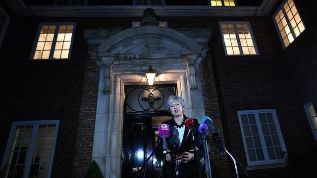 May spricht vor einem Haus des nächtens in Mikrofone.