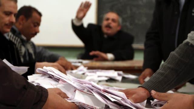 Männer sortieren Stimmzettel