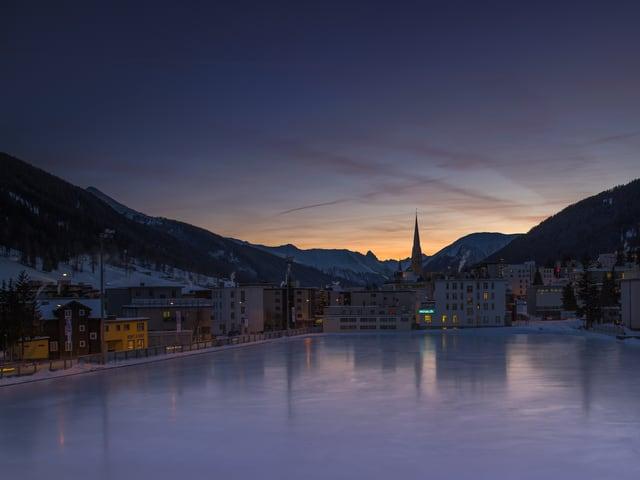 Grosse Eisfläche mit Häusern des Dorfs am Rand. Es ist Dämmerung, alles ist in dunklen violett Tönen. Am Horizont zwischen Alpengipfeln ist der Himmel heller.
