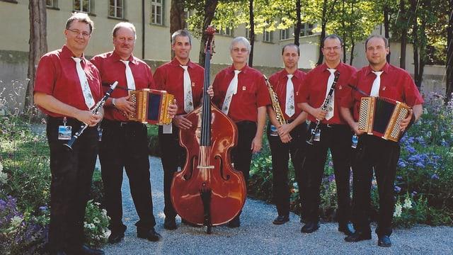Kapelle in roten Hemden mit Instrumenten in der Stadt Chur in einem Park.
