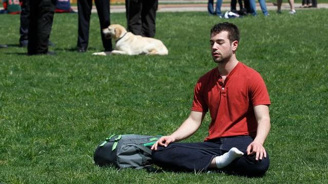 Ein Mann sitzt auf einer Wiese und meditiert.
