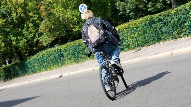Jugendlicher fährt mit seinem Velo über die Strasse.