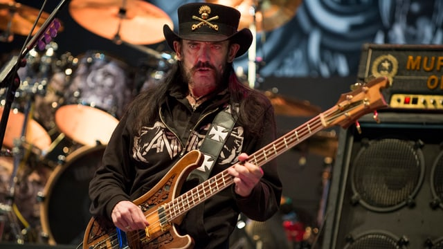 Lemmy Kilmister mit Gitarre an einem Konzert.