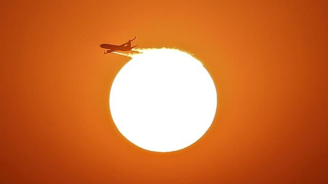 Ein Flugzeug fliegt vor der untergehenden Sonne.