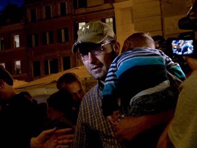 Mann mit schlafendem Kind auf dem Arm