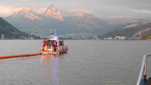 Polizeiboot legt Ölsperre aus.