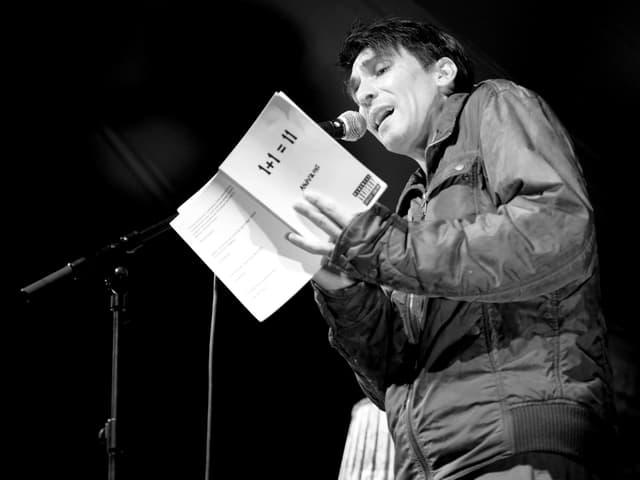 Ein Mann steht auf einer Bühne, hält ein weisses Buch in der Hand und spricht in ein Mirkofon.