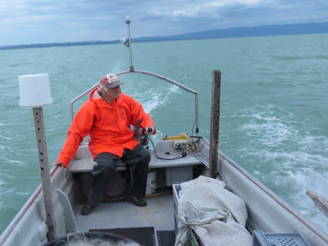 Mann in Fischerboot auf dem See.