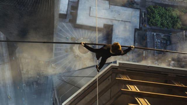 Vogelperspektive: Mann auf einem Seil mit Balancierstab.