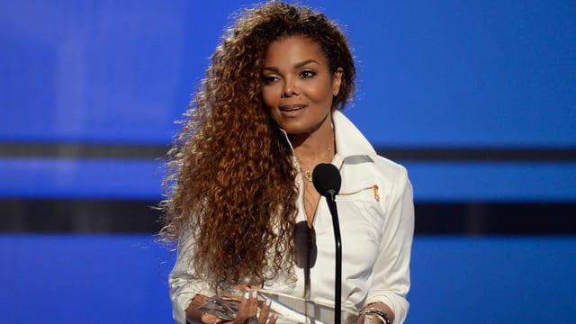 Janet Jackson in weisser Bluse mit wallender Haarpracht