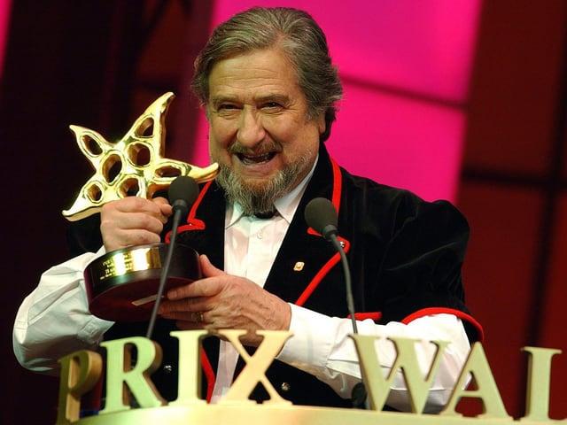 Ein lachender Mann hält eine sternförmige Auszeichnung in der Hand.