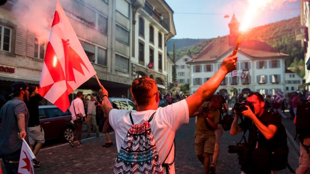 Ein Mann mit Feuerwerk in der einen und einer Jura-Fahne in der anderen Hand.