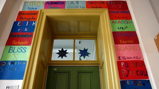 handgeschriebene Plakate in unterschiedlichen Sprachen rahmen eine Schultüre ein.