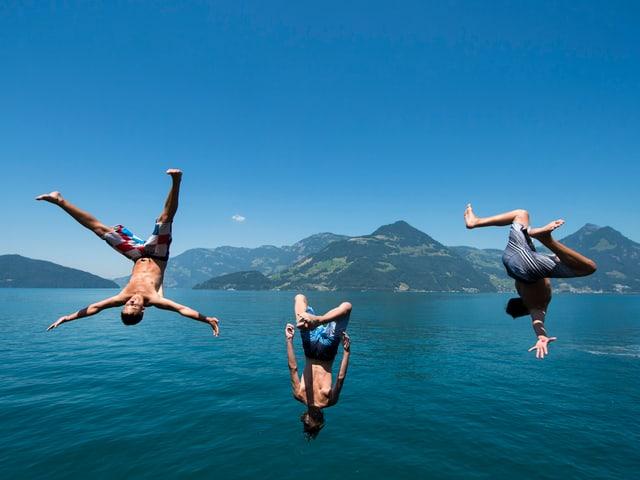 Drei junge Männer springen bei Beckenried in den Vierwaldstättersee