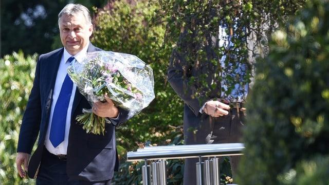 Viktor Orban hält einen Blumenstrauss.