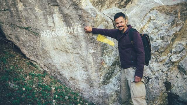 Moderator Pät lehnt sich an einen Felsen, auf dem «Parkgrenze» steht.