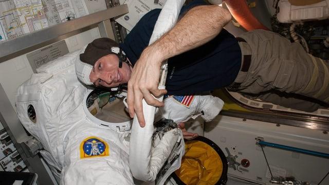 Mike Hopkins neben seinem Anzug, er schwebt in der Horizontalen.