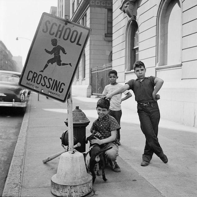 Drei Kinder auf der Strasse. Sie stehen neben einem Schild mit der Aufschrift «School Crossing».