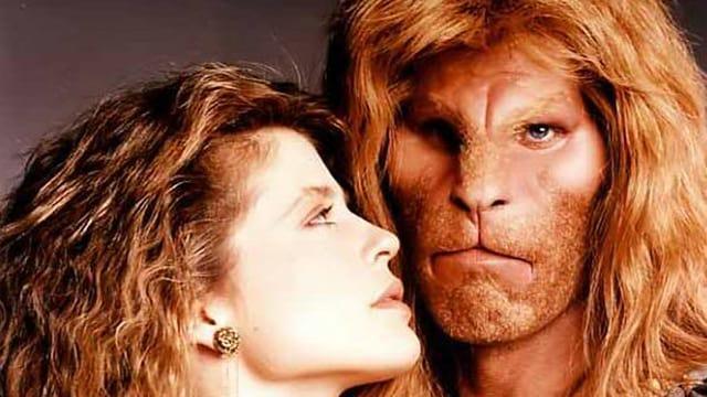 Ein Mann mit einem löwenähnlichen Gesicht und langen Haaren steht neben einer jungen Frau
