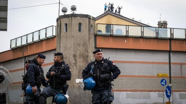 Gefängnis in Mailand mit davor stehenden Polizisten und Insassen auf dem Dach.