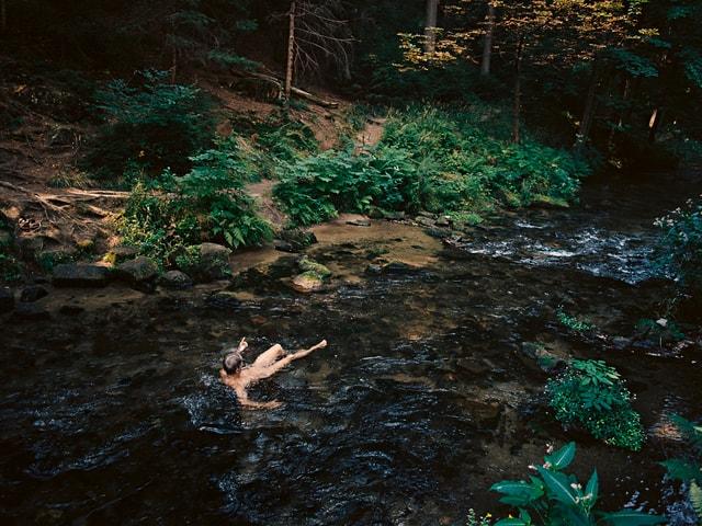 Ein nackter Mann badet in einem Fluss.