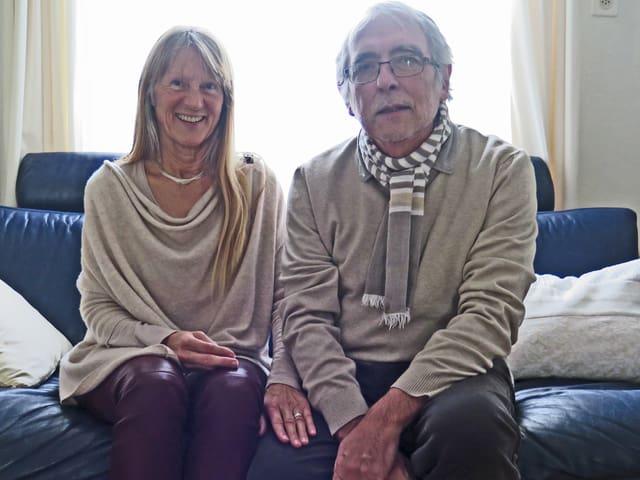 Das Ehepaar sitzt auf einem dunklen Sofa aus Leder.