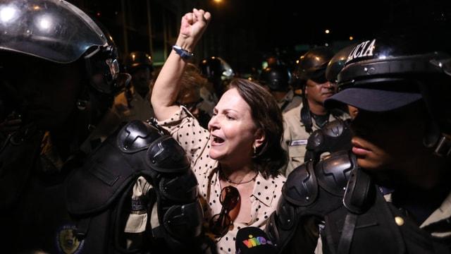 Frau Ledezma mit erhobener Faust, vor ihr zwei Polizisten in voller Kampfmontur.