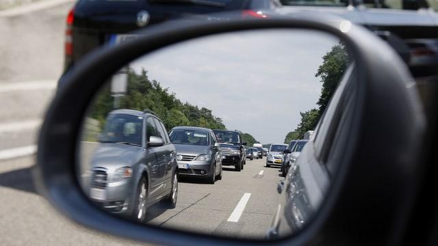 Autoschlange, zu sehen im Rückspiegel eines Autos