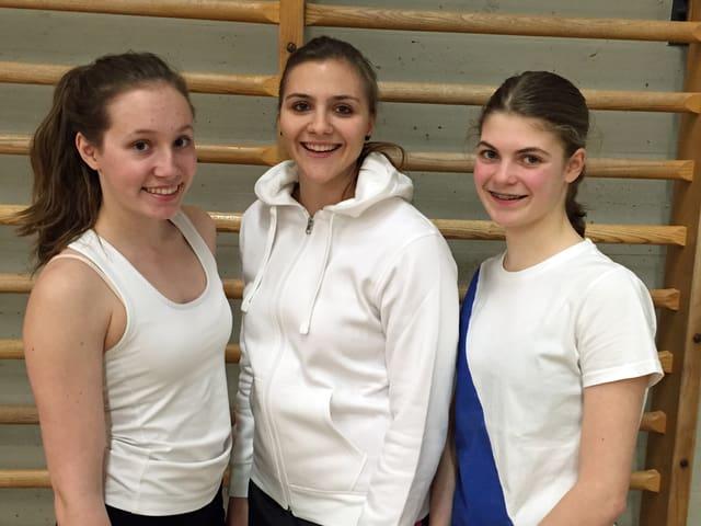 drei junge Frauen in Sportkleidern