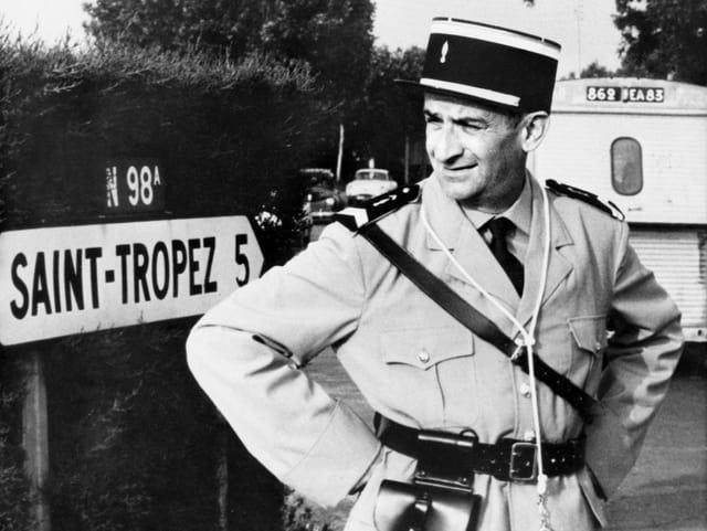 De Funès steht als Polizist vor einem Ortsschild von Saint Tropez.