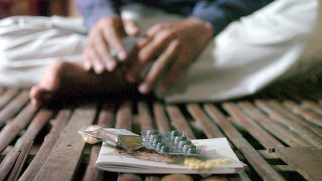 Ein Mann sitzt am Boden, vor sich Medikamente.