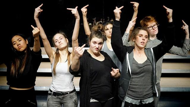 Junge Frauen auf einer Theaterbühne zeigen dem Publikum den STinkefinger.
