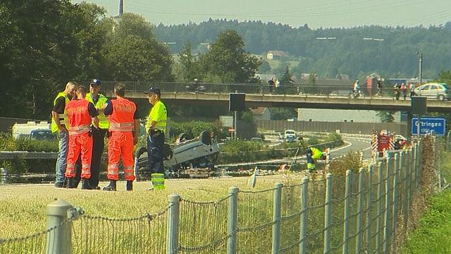 Uniformierte Herren, im Hintergrund das auf dem Dach liegende Unfallauto.
