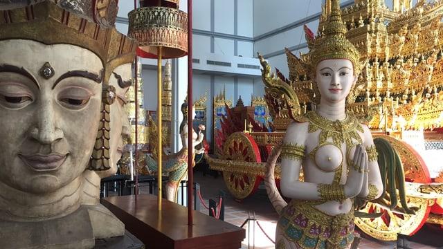 Thailändische Gottheits-Figuren und der goldene Wagen im Hintergrund.