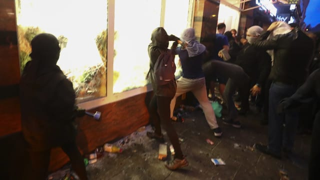 Vermummte Personen schlagen auf Schaufenster ein.