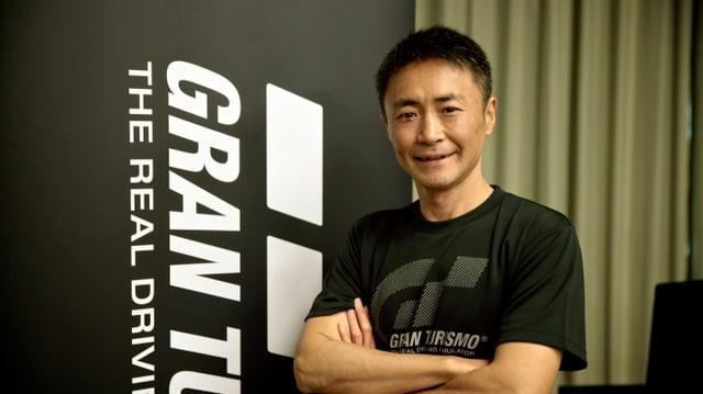 Yamauchi posiert vor dem Logo seines Spiels.