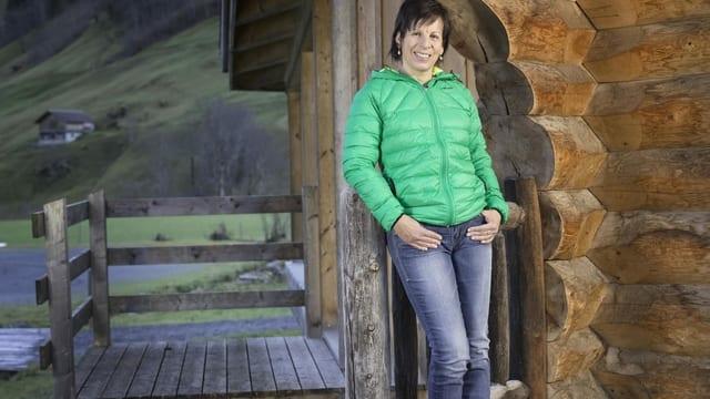 Frau in grüner Skijacke lehnt sich an Holzpfahl.