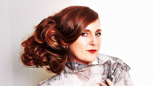 Eine Frau mit rotem Haar, zur Site gekämmt, die LIppen rot geschminkt.