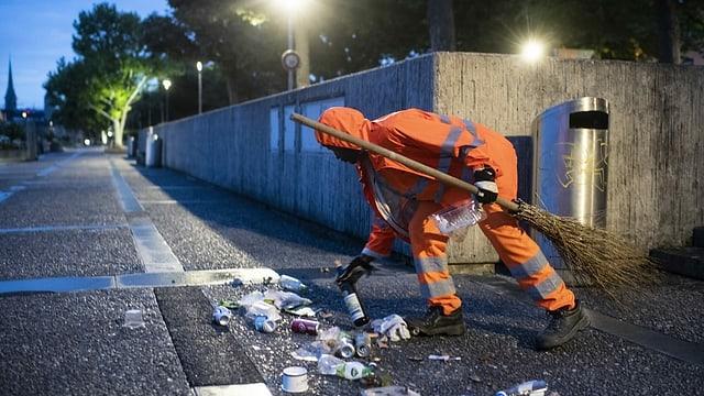 Ein Mann mit oranger Kleidung sammelt Abfälle vom Boden auf.