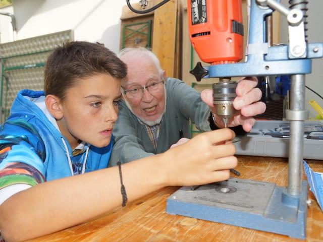 Ein Bub und ein älterer Mann vor einer Bohrmaschine.