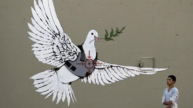 Eine auf eine Wand gemalte Friedenstaube mit einem Olivenzweig im Schnabel. Sie trägt eine schusssischere Weste.
